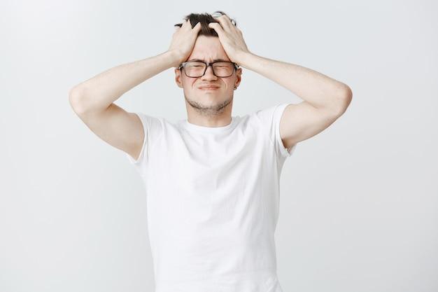 Ein besorgter und erschöpfter junger mann packt den kopf und schließt die augen vor dem überdenken Kostenlose Fotos