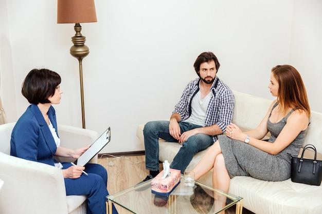 Ein bild der paare, die zusammen auf sofa sitzen und miteinander sehr ernst schauen. doktor betrachtet sie und hält papiertablette in den händen. Premium Fotos