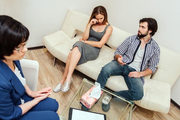 Ein bild der umkippenfrau sitzend auf sofa und schreiend. sie wischt sich die augen. bärtiger mann sieht sie an. er ist auch verärgert. doktor sitzt vor ihnen und schaut nach unten. Premium Fotos