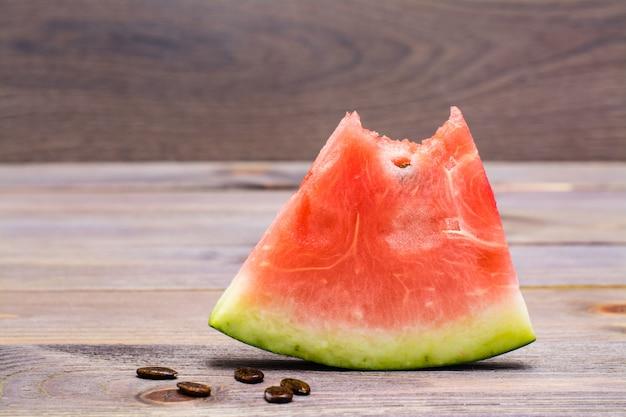 Ein bisschen wassermelone und wassermelonenkerne auf holztisch Premium Fotos