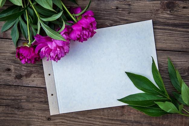 Ein blatt papier und einige rosa pfingstrosen auf hölzernem hintergrund mit kopienraum als postkarte Premium Fotos