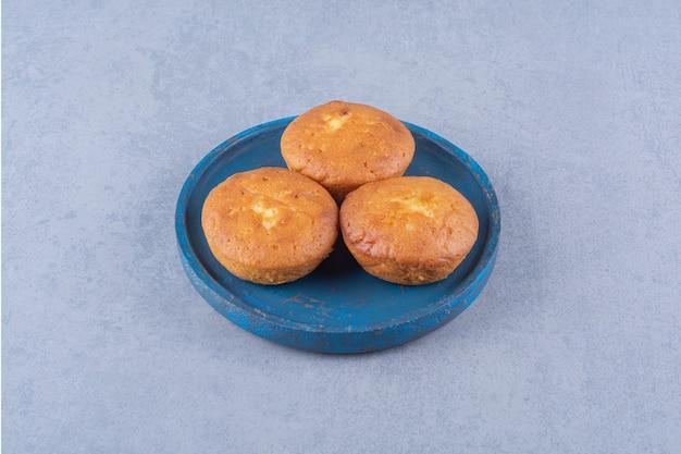 Ein blaues holzbrett mit drei süßen frischen cupcakes. Kostenlose Fotos