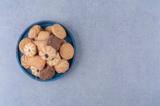 Ein blaues holzbrett mit süßen runden leckeren keksen auf sackleinen. Kostenlose Fotos