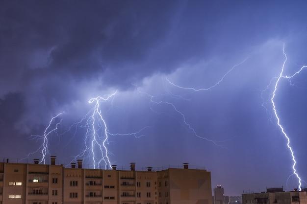 Ein blitz über der stadt am nachthimmel trifft das dach des hauses. Premium Fotos