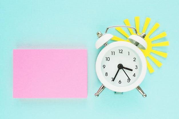 Ein block von rosa aufklebern, ein weißer wecker und eine gelbe papiersonne, die von hinten auf einen hintergrund des blauen papiers späht. Premium Fotos
