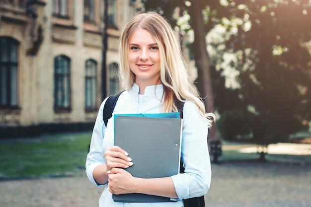 Ein blondes studentenmädchen lächelt und hält einen ordner und ein notizbuch in ihren händen auf einem hochschulhintergrund Premium Fotos