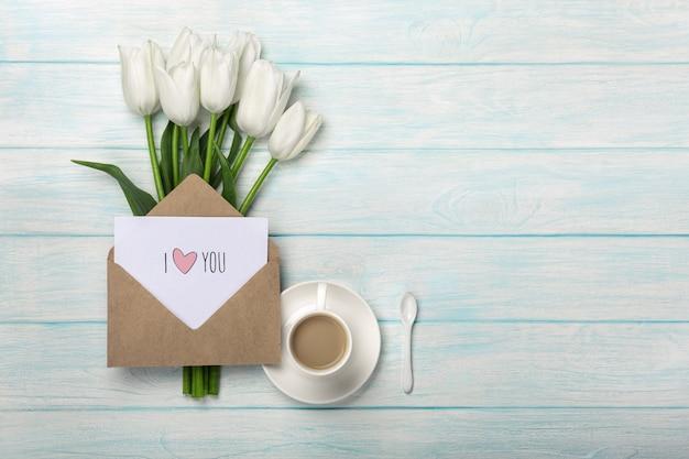 Ein blumenstrauß von weißen tulpen und von tasse kaffee mit einer liebesanmerkung auf blauen hölzernen brettern Premium Fotos