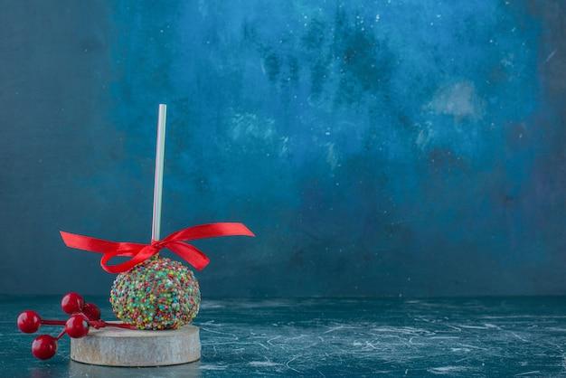 Ein bonbonbeschichteter lutscher und eine weihnachtsbeerenverzierung auf einem stück holz auf blauem hintergrund. hochwertiges foto Kostenlose Fotos