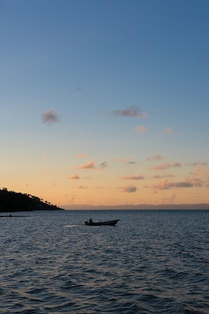 Ein boot in der mitte der bucht mit einem sonnenuntergang dahinter Premium Fotos