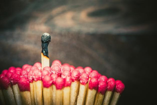 Ein brennendes streichholz hebt sich von der masse ab Premium Fotos