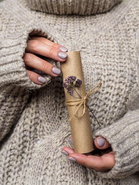 Ein brief mit einer blume oregano in den händen eines mädchens geschmückt. ein mädchen in einem wollpullover hält einen brief aus kraftpapier. vor dem urlaub atmosphäre Premium Fotos