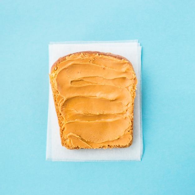 Ein brottoast geschmiert mit erdnussbutter auf blauem grund Premium Fotos