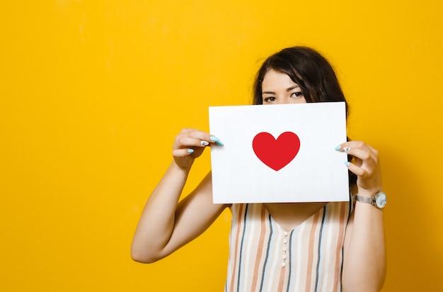 Ein brunettemädchen, das ein weißes leerzeichen mit einem inneren auf einer gelben wand anhält Premium Fotos