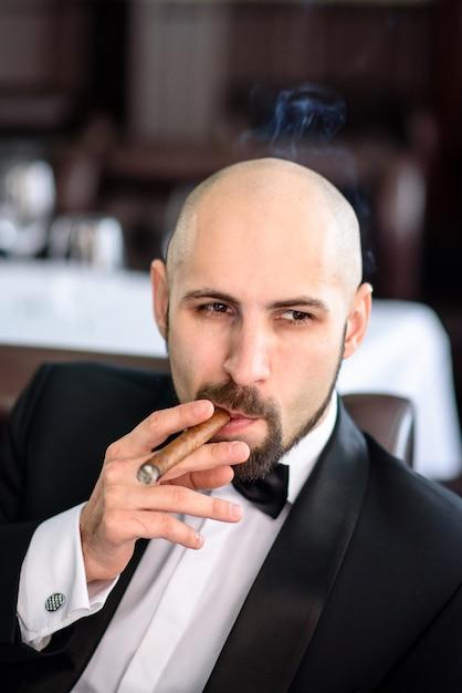 Ein brutaler mann im anzug raucht eine zigarre. Premium Fotos