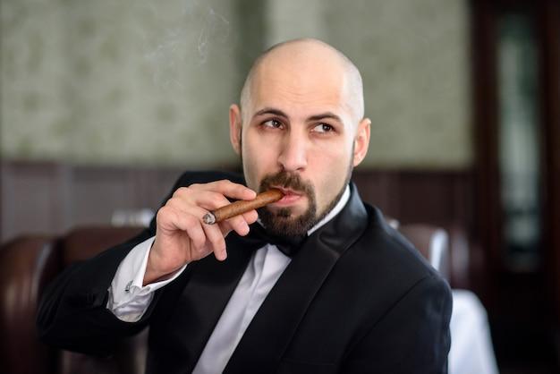 Ein brutaler mann im frack raucht eine zigarre. Premium Fotos