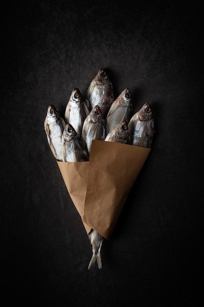 Ein bündel trockenfisch auf einem schwarzen hintergrund mit kraftpapier Premium Fotos