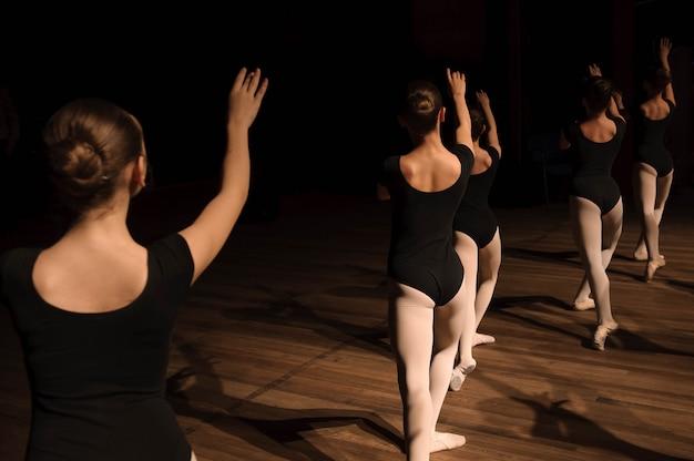 Ein choreografierter tanz einer gruppe anmutiger hübscher junger ballerinas, die auf der bühne einer klassischen ballettschule üben Premium Fotos