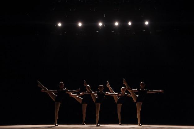 Ein choreografierter tanz einer gruppe anmutiger hübscher junger ballerinas, die auf der bühne üben Premium Fotos