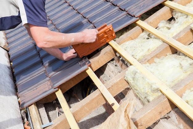 Ein dachdecker, der fliese auf das dach legt Premium Fotos