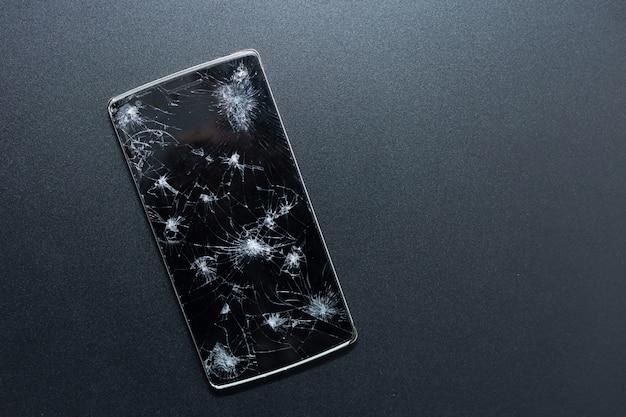 Ein defektes telefon auf schwarzem hintergrund. zerquetschtes gerät mit dem defekten schirm, der einen unfall darstellt. strukturierter bildschirm mit beschädigungen. dunkles glas eines bildschirms, zerbrochen. Premium Fotos