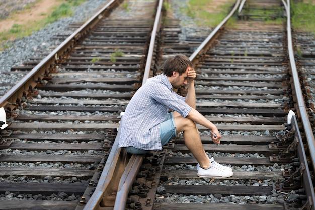 Ein depressiver mann, der auf den eisenbahnschienen sitzt und ein telefon in der hand hält, trifft eine schwierige entscheidung, in der vergangenheit zu leben oder seine zukunft zu ändern Premium Fotos