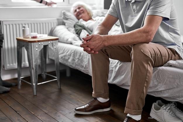 Ein depressiver mann sitzt in der nähe seiner kranken älteren frau und liegt krank im bett. im krankenhaus Premium Fotos