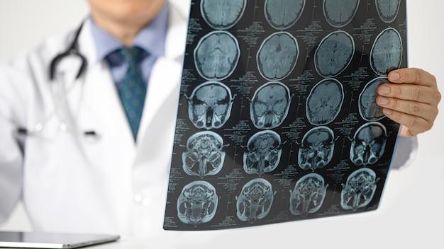 Ein doktor, der einen mri-scan betrachtet Premium Fotos