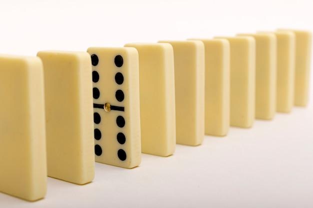 Ein domino, der sich von der reihe abhebt. dominosteine auf weiß Premium Fotos