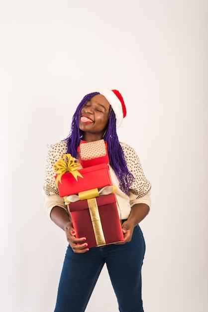 Ein dunkelhäutiges glückliches mädchen hält viele roten geschenke in ihren händen. Premium Fotos