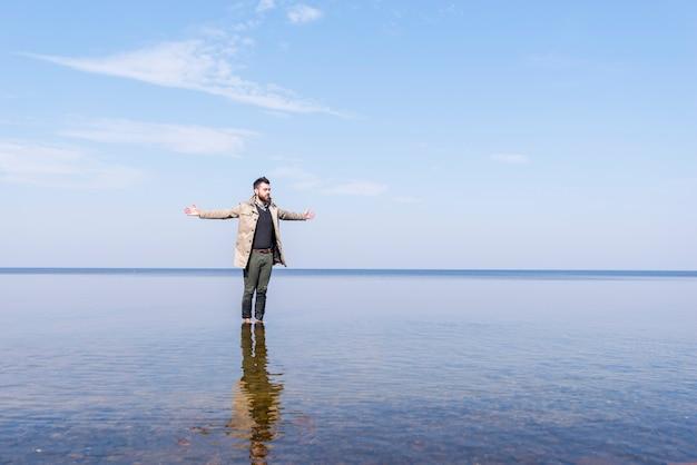 Ein einsamer junger mann streckte die hand aus und stand im seichten meerwasser Kostenlose Fotos
