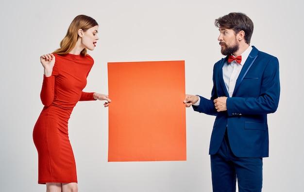 Ein eleganter mann im anzug und eine frau in einem roten kleid mit einer mohnblume in der hand ein plakat für eine Premium Fotos