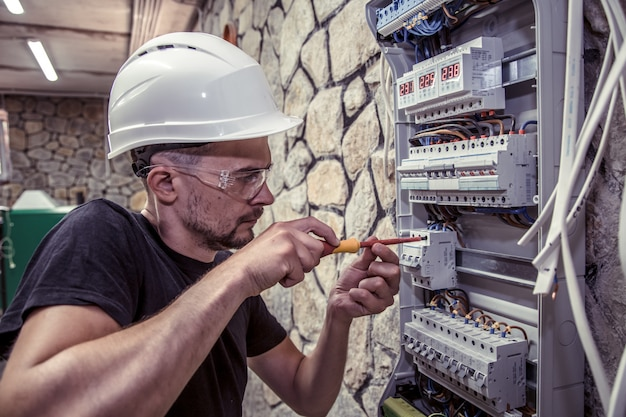 Ein elektriker arbeitet in einer schalttafel mit einem elektrischen verbindungskabel Kostenlose Fotos