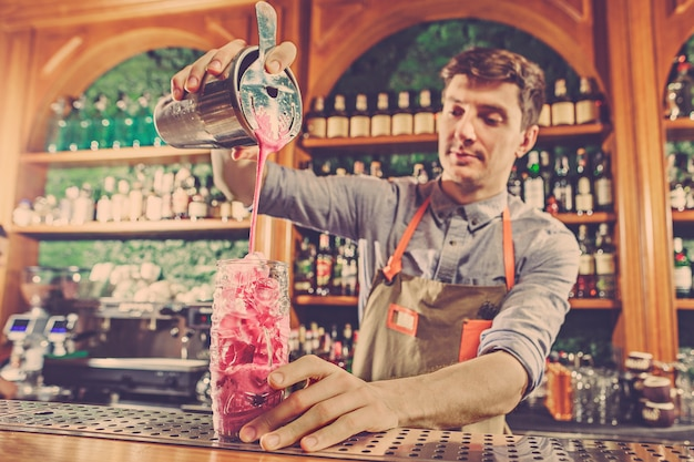 Ein erfahrener barmann macht einen cocktail im nachtclub. Kostenlose Fotos