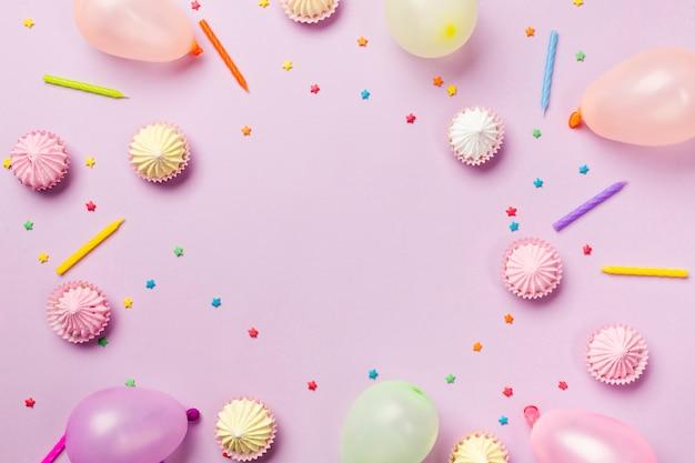Ein erhöhter blick auf streusel; kerzen; ballons; aalaw auf rosa hintergrund Kostenlose Fotos