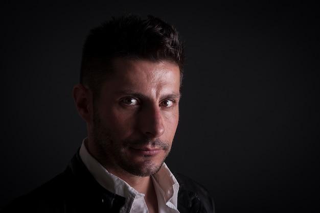 Ein ernster kaukasischer mann auf dunklem hintergrund Premium Fotos