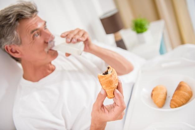 Ein erwachsener mann im raum isst und ruht sich aus. Premium Fotos