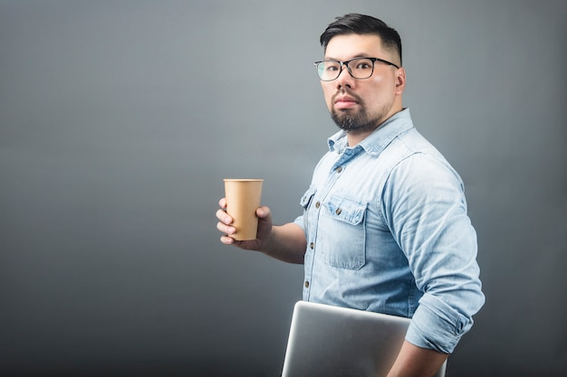 Ein fälliger mann, der einen computer und einen kaffee anhält Premium Fotos