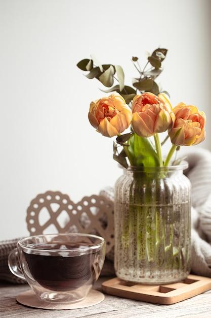 Ein festliches stillleben mit einem blumenarrangement in einer vase und einer tasse tee und gemütlichen dingen. Kostenlose Fotos