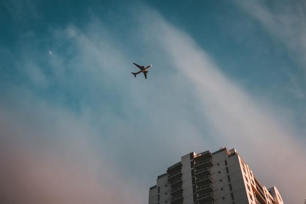 Ein flugzeug fliegt über ein gebäude Kostenlose Fotos