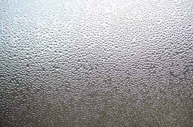 Ein foto der glasoberfläche des fensters, bedeckt mit einer vielzahl von tröpfchen unterschiedlicher größe. hintergrundbeschaffenheit einer dichten kondensatschicht auf glas Premium Fotos