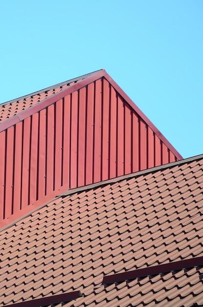 Ein fragment eines dachs aus einer metallfliese von dunkelroter farbe. qualität dachdecker Premium Fotos