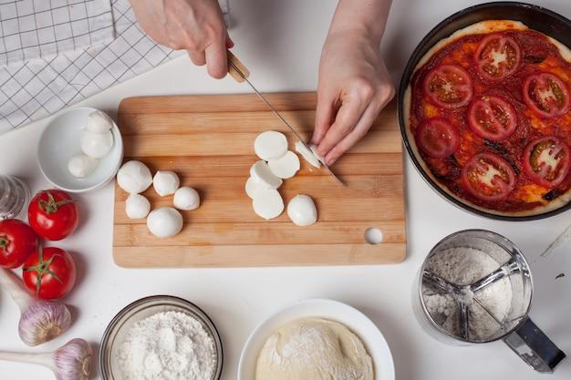 Ein frauenkoch schneidet mozzarella-käse. Premium Fotos
