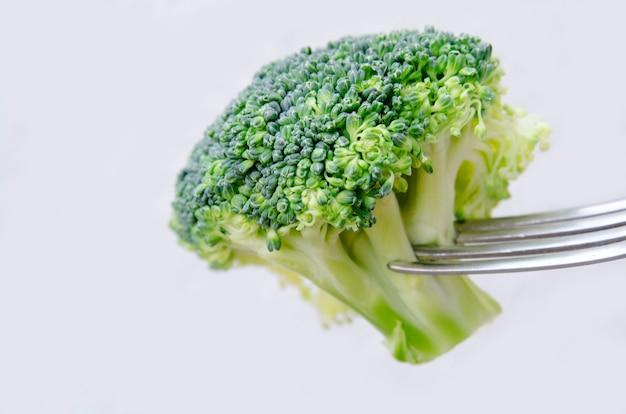 Ein frischer brokkoli reif auf der gabel oben lokalisiert auf weiß, abschluss. bite des rohen brokkolisalats Premium Fotos