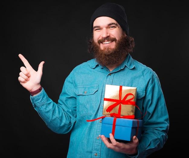 Ein fröhlicher junger bärtiger hipster hält einige geschenke und schaut lächelnd in die kamera und zeigt weg Premium Fotos