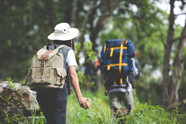 Ein fröhlicher wanderer geht mit einem rucksack durch den dschungel. Kostenlose Fotos