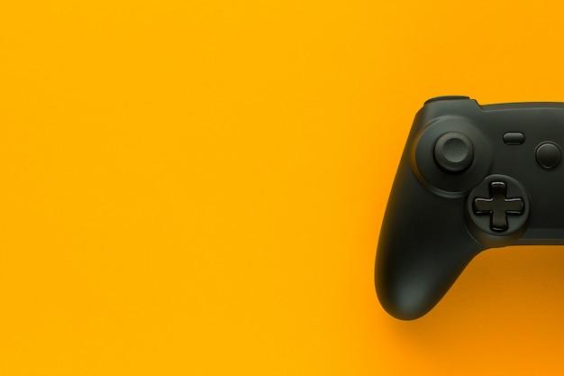 Ein gamepad auf einem gelben tisch und kopierplatz Premium Fotos