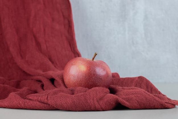 Ein ganzer roter frischer apfel auf einem tuch. Kostenlose Fotos