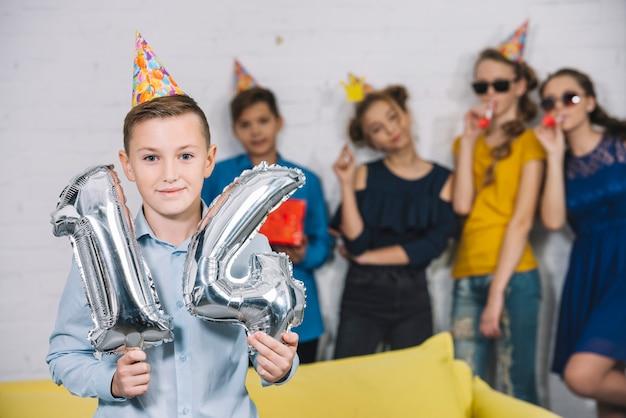 Ein geburtstagsjunge, der silberne ballone der zahl 14 der folie mit seinen freunden stehen hinter ihm hält Kostenlose Fotos