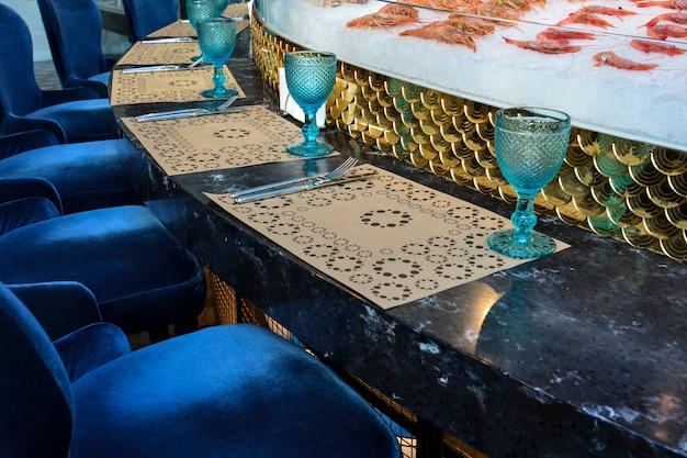 Ein gedienter runder tisch, der sich um die offene küche in einem fischrestaurant befindet. Premium Fotos