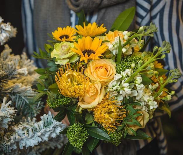 Ein gelber strauß von sonnenblumen und rosen in den händen einer dame Kostenlose Fotos